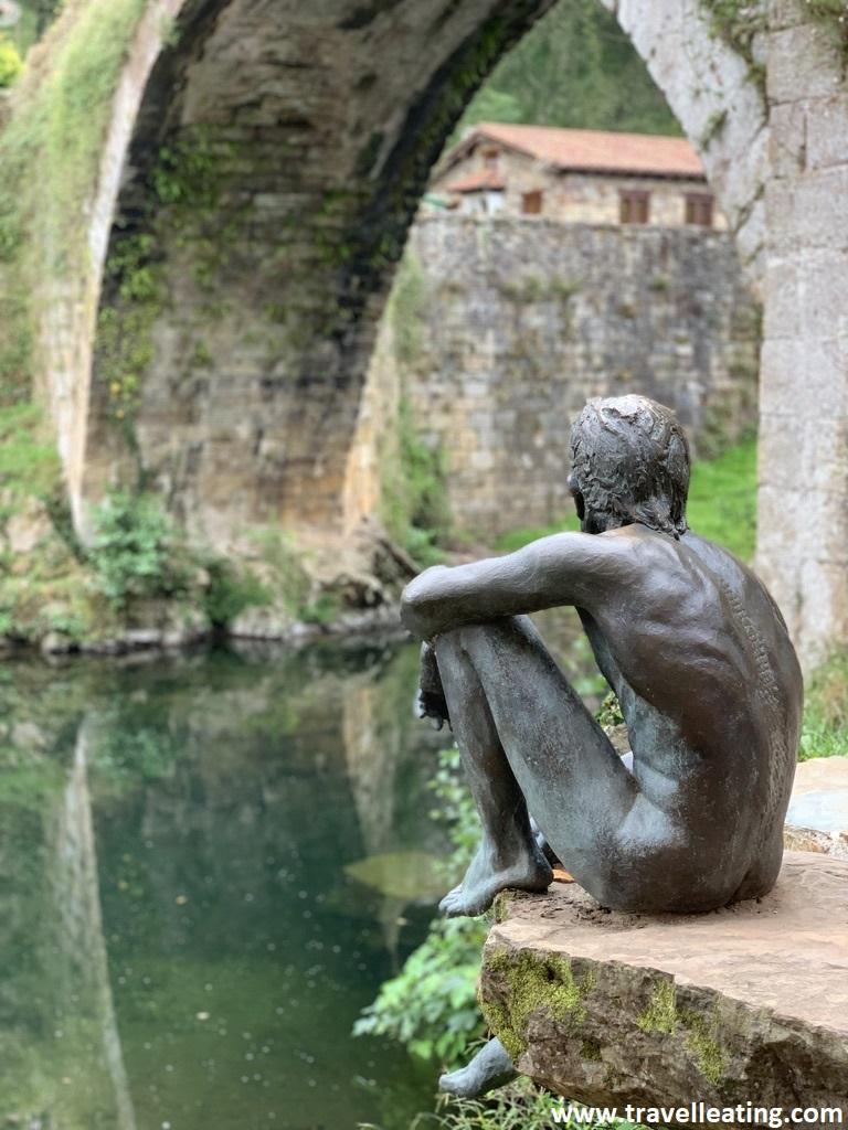 Estatua de un hombre sentado junto al río, al lado de un puente de piedra que se refleja en el agua.