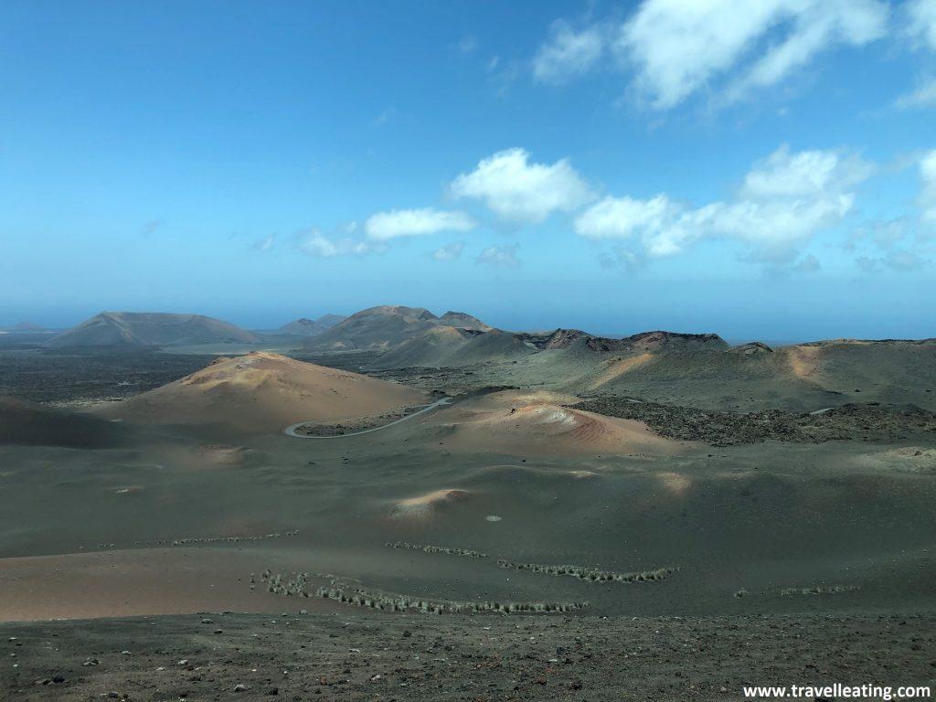 Conjunto de volcanes en medio de una tierra negra, ocre y rojiza, que contrasta con el azul del cielo. El Parque Nacional de Timanfaya es otro de los imprescindibles que ver en Lanzarote.