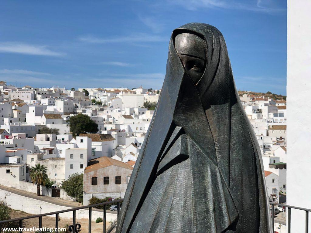 Escultura de una monja tras situado en un balcón donde se observa el pueblo de Vejer de la Frontera