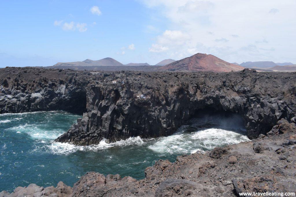 Tramo de costa formado por riscos y acantilados de roca volcánica repletos de cavidades y cuevas, tras el cual se observa un paisaje volcánico.
