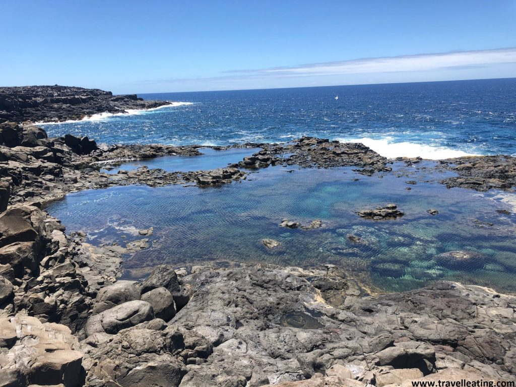 Piscina natural de agua turquesa rodeada por rocas volcánicas negras frente al mar.