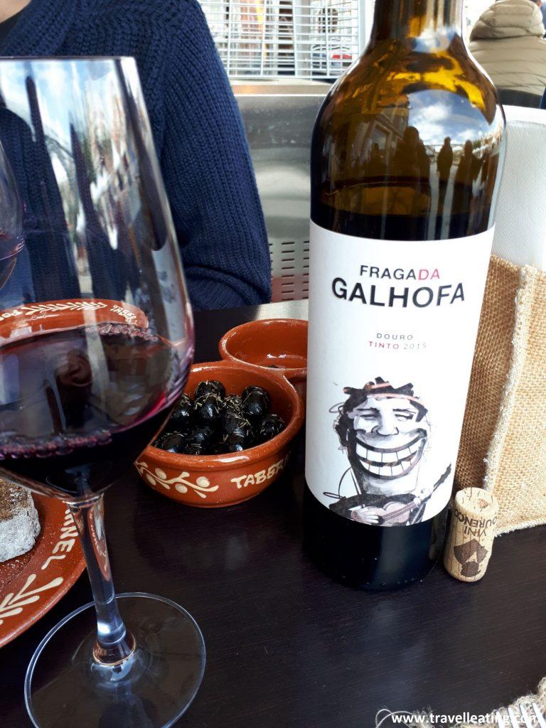 Aperitivo servido en una mesa junto a una botella de vino tinto.