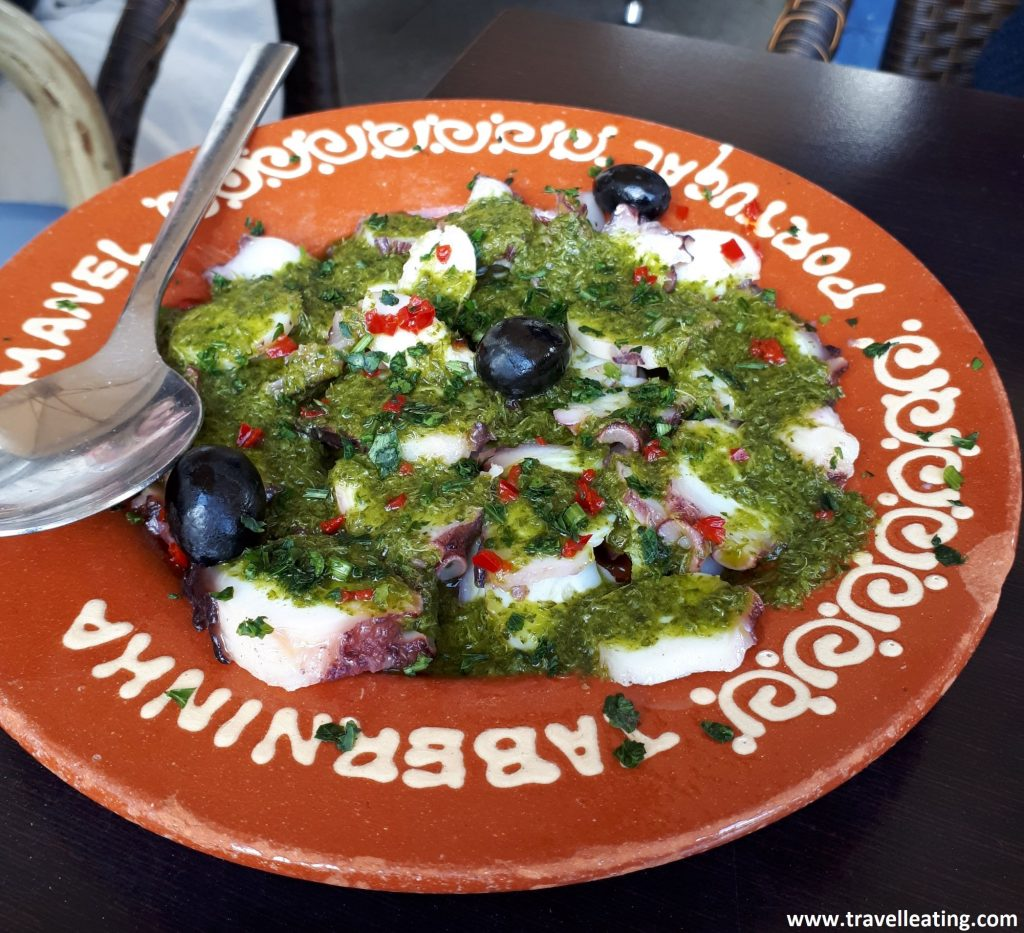 Pulpo laminado servido en un plato de cerámica con salsa verde por encima.