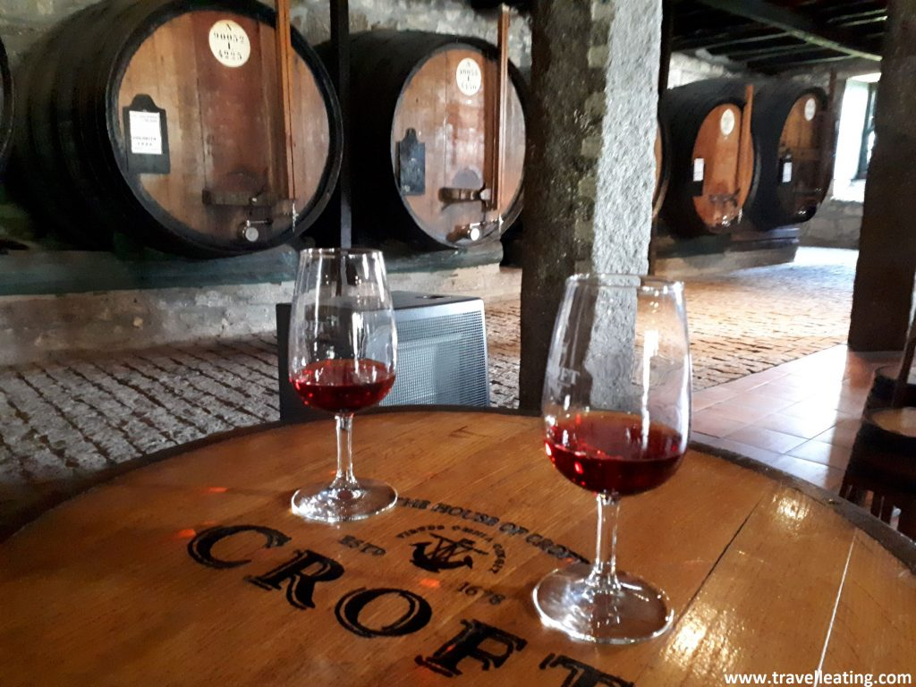 Dos copas de vino do Porto encima de un barril de madera, en una bodega.