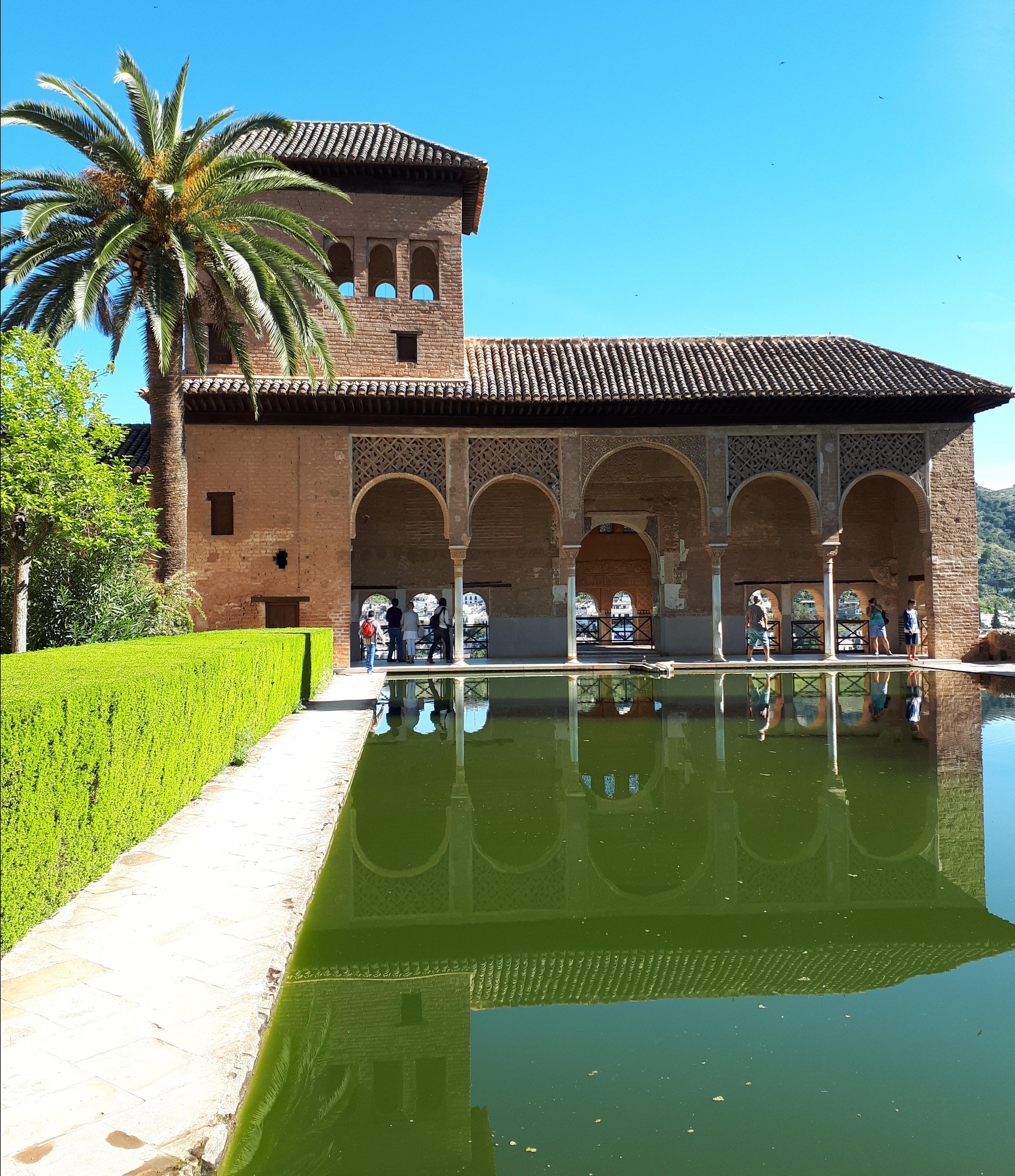 Jardín de la Alhambra con un estanque verde en el cual se refleja uno de los edificios con conforman este monumento.