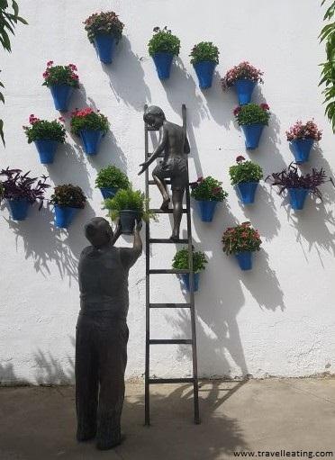 Escultura de un niño subido a una escalera y mirando a un abuelo que se encuentra debajo sujetándole una maceta. En la pared vemos varias macetas azules repletas de flores. Es otro monumento importante de ver en Córdoba.