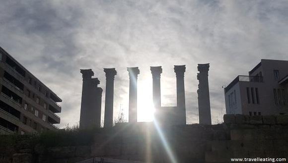Templo romano compuesto de varias columnas sin techo, en medio de una calle de una ciudad.