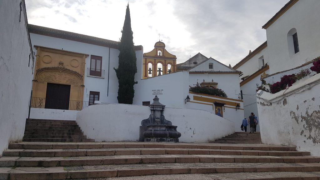 Preciosa cuesta con una gran escalera detrás de la cual destaca el bonito campanario de una iglesia.