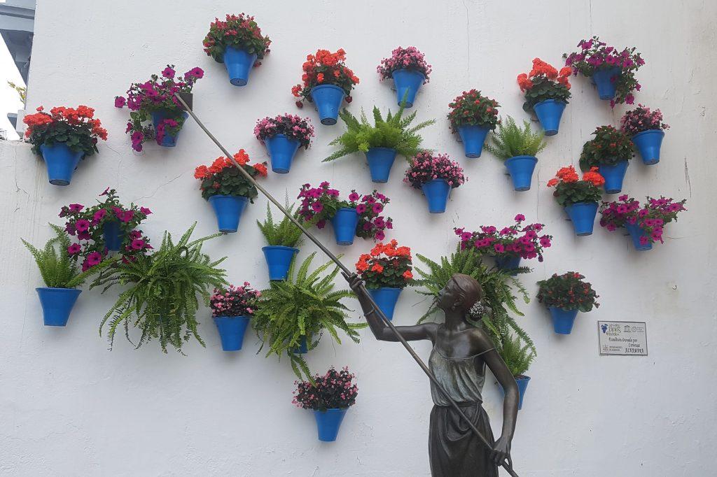 Escultura de una mujer regando unas flores colgadas de la pared en unas macetas, la cual es un homenaje a los patios cordobeses. Se trata de uno de los imprescindibles que ver en Córdoba.