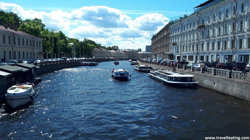 Imagen de uno de los canales de San Petersburgo, hecha desde uno de los puentes que lo cruzan. En él vemos un par de barcos circulando y gente paseando por las orillas. A lado y lado de éste encontramos edificios.