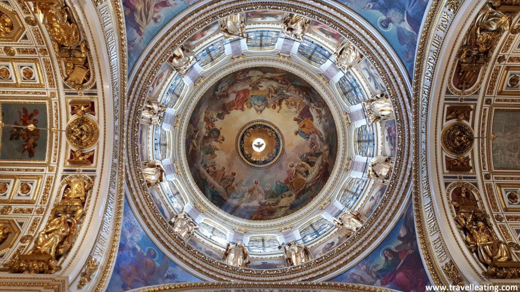 Un techo interior de la Catedral de San Isaac. En el centro encontramos una bóveda con imágenes religiosas en medio e iluminada de las ventanas que la rodean. Destaca el color blanco con los detalles dorados, así como el azul en las pinturas.