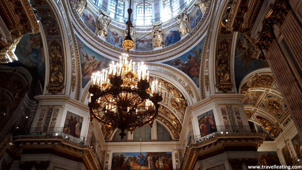 Interior de la Catedral de San Isaac. En este vemos una de las bóvedas principales con una gran lámpara dorada en el medio. Las paredes están repletas de imágenes religiosas y las columnas blancas están adornadas con relieves dorados.