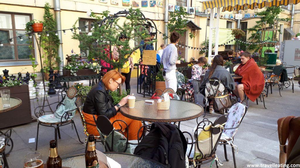 Terraza del restaurante en el que vemos varias mesas ocupadas de gente en un patio interior. Todo él está muy bien decorado y con muchas plantas.