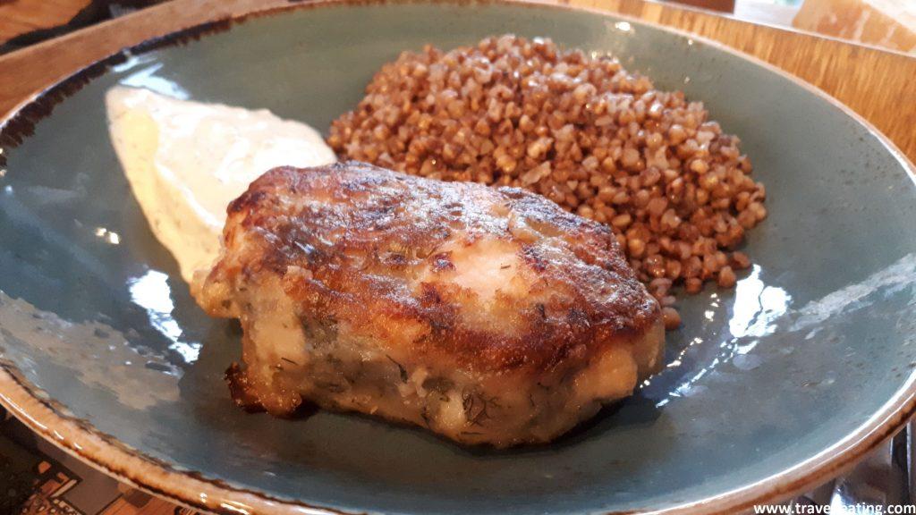 Vemos un plato con una especie de hamburguesa de pescado acompañada de trigo sarraceno y de crema agria