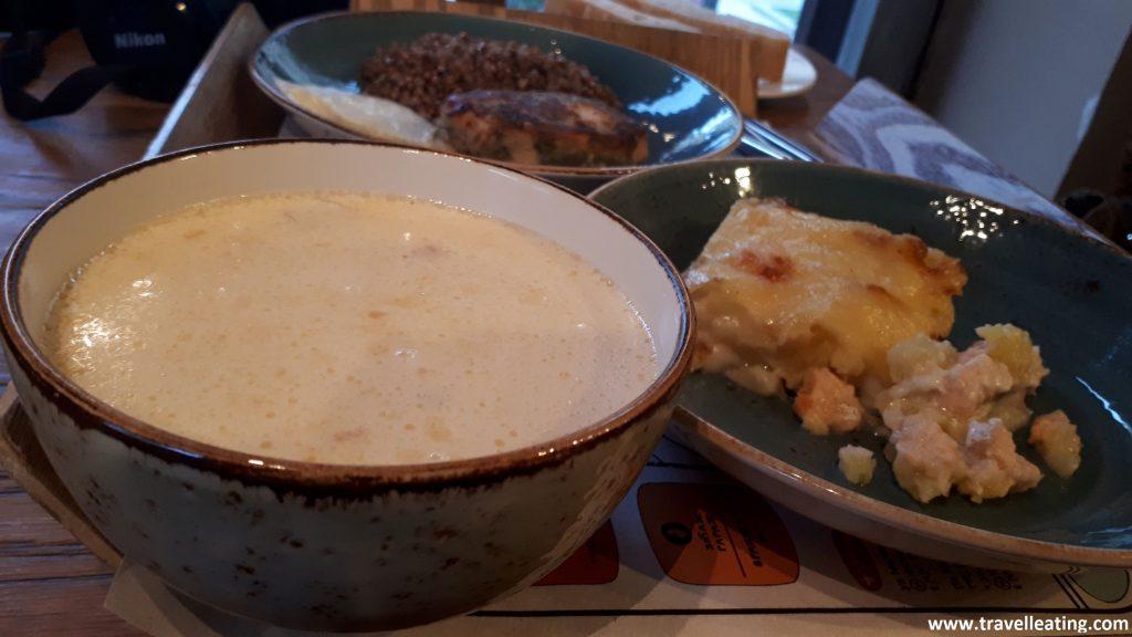 En la foto se ve una bandeja sobre la cual hay un cuenco con una sopa blanca de coliflor, un plato con un pastel de patata y salmón y otro plato al fondo con más comida.