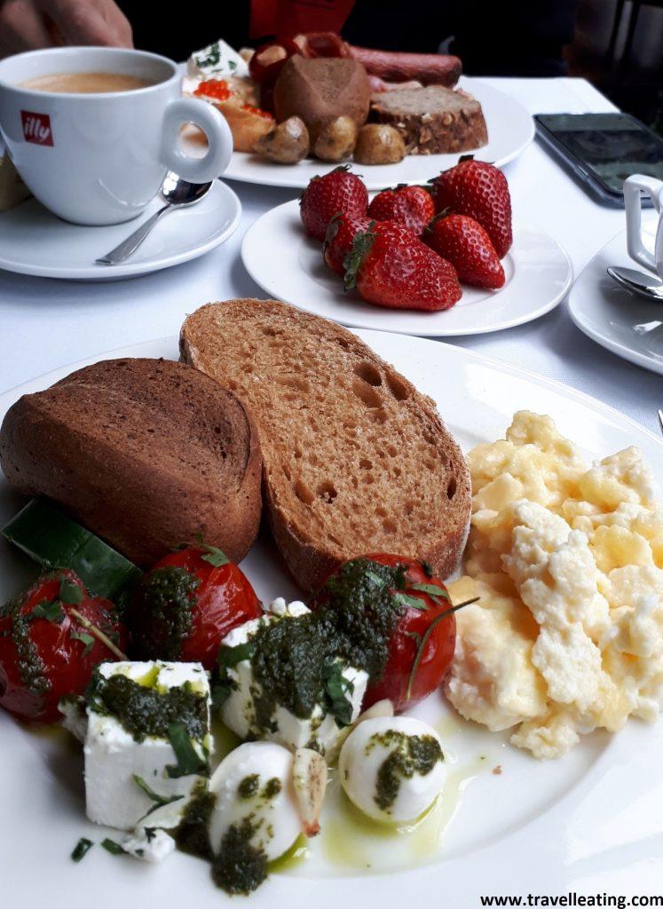 Foto del desayuno del hotel. Vemos un plato en un primer plano con dos panes diferentes, huevos revueltos y una ensalada de tomate, queso y pesto. En el medio de la mesa destaca un plato de fresas, justo al lado de la taza de té y de otra con café.