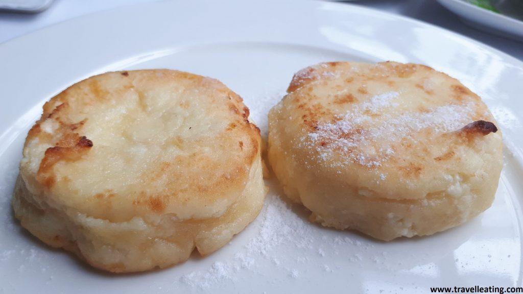 Pequeños pancakes de requeson, pequeños y gruesos con azúcar glaseado por encima.