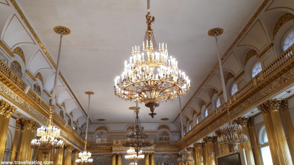 Techo de una de las salar interiores del Hermitage. Se trata de una sala blanca con columnas y detalles dorados y unas increíbles lámparas de cristal colgando del techo.