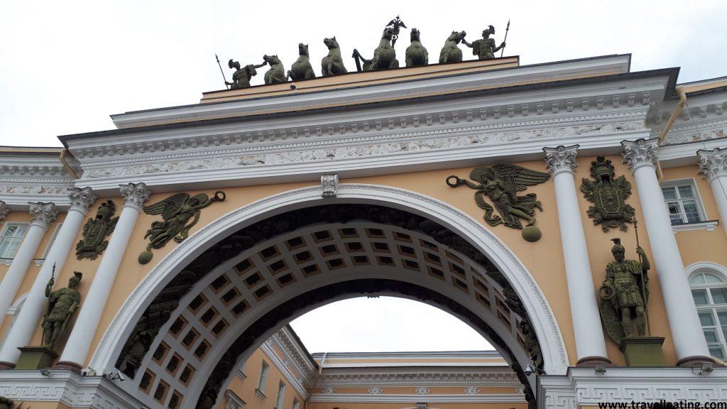 Arco de la Plaza del Palacio, de color amarillo pastel y detalles blancos (como los relieves y las columnas). Encima de este vemos varias esculturas de guerra, dos ángeles a cada lateral, y un carro de guerra rodeado de caballos justo encima del arco.