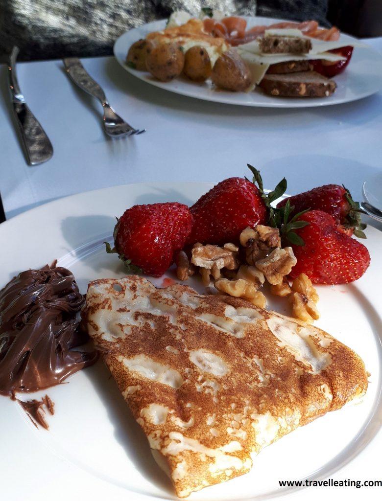 Foto del desayuno donde destaca el plato en primer plano con una crep doblada de la que sale nutela, y acompañada de fresas y nueces.