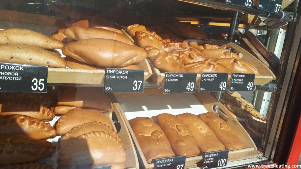 Se ve un mostrador de una tienda repleto de empanadillas grandes con diferentes rellenos y formas.