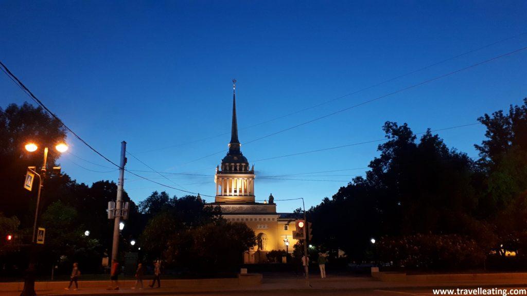 Se ve una plaza del centro de San Petersburgo con un edificio muy bonito amarillento, con una torre acabada en pico, tipo iglesia. El cieo está medio oscuro, como si estuviera atardeciendo, con una luz tenue. Sin embargo ya era de noche y no había oscurecido por ser la época de las Noches Blancas.