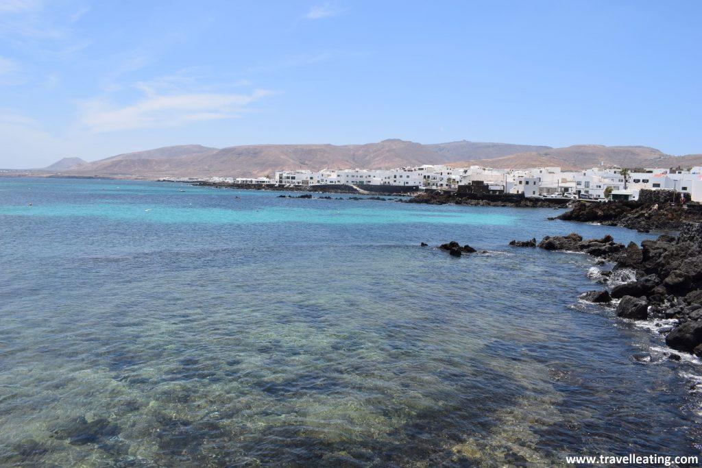 Precioso pueblo de casas blancas situado frente a una bahía formada por piedra volcánica negra y pequeñas piscinas naturales, frente a un mar turquesa.