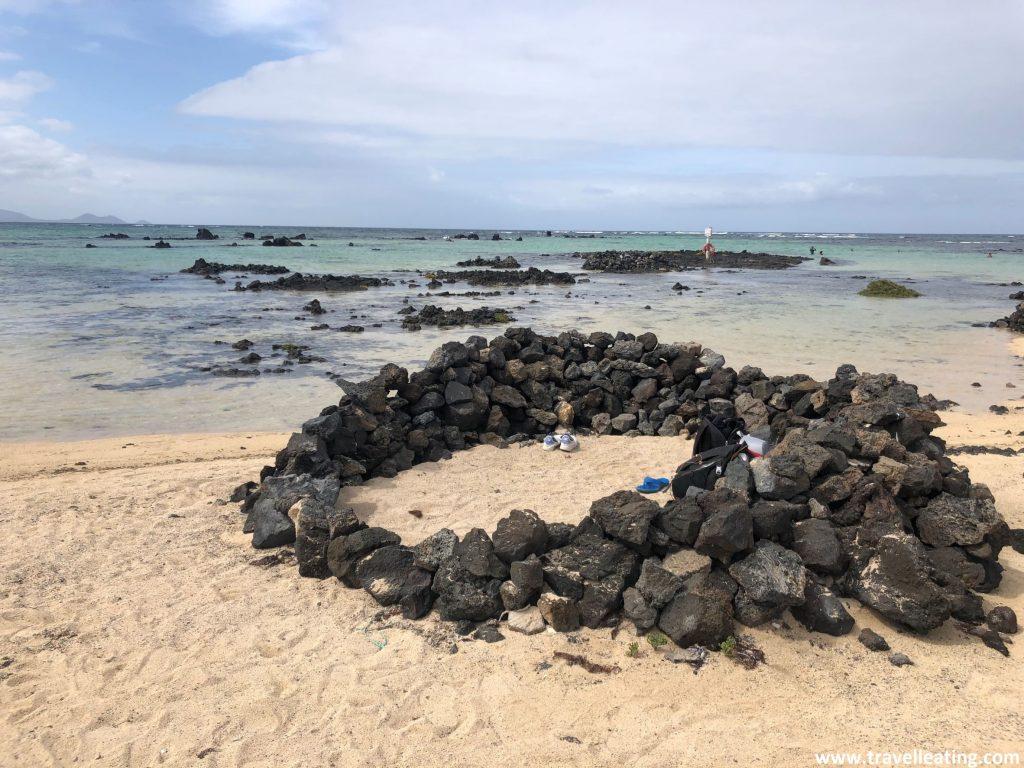 Preciosa playa de arena blanca y aguas turquesas, que presenta un refugio circular hecho con piedras volcánicas negras en la arena.