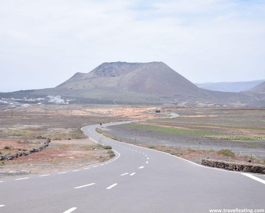 Vistas de una carretera sinuosa tras la cual se alza un imponente volcán con tonos verdosos. El Volcán la Corona, otro de los lugares que ver en Lanzarote.