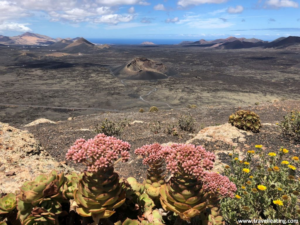 Increíbles vistas de un volcán negro en medio de una tierra volcánica salpicada por otros volcanes. Una de las vistas más espectaculares que ver en Lanzarote.