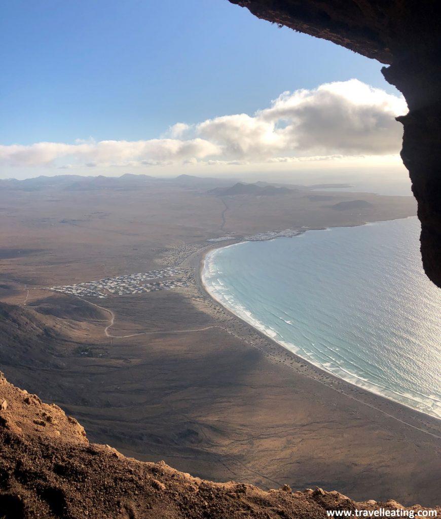 Vistas de una playa extensa custodiada por un risco y un pueblo blanco, vista desde lo alto de un acantilado, en el interior de una cueva que se abre al mar.