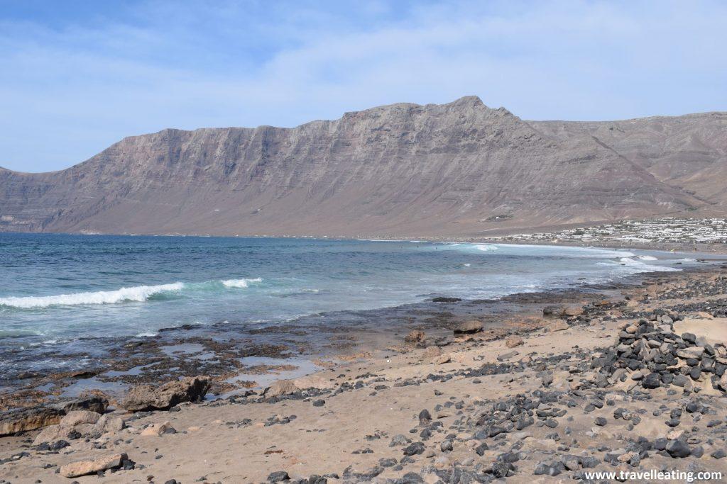 Extensa playa de arena tostada y fuerte oleaje al final de la cual se alza un impresionante risco montañoso.