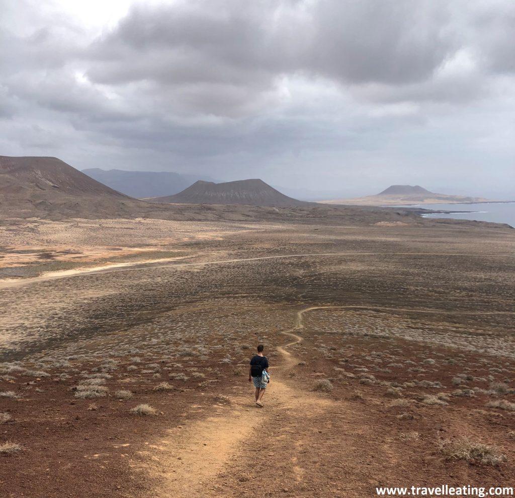 Vistas de una preciosa isla volcánica desde lo alto de uno de sus volcanes. Vemos un chico descendiendo por el camino que baja de esta ladera de arenas rojizas volcánicas.