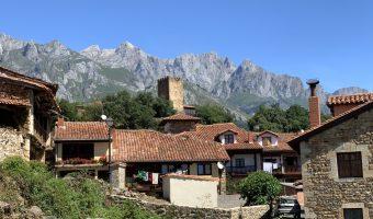 Pueblo de montaña con una torre en medio y las montañas alzándose detrás. Es uno de los pueblos más bonitos de Cantabria.