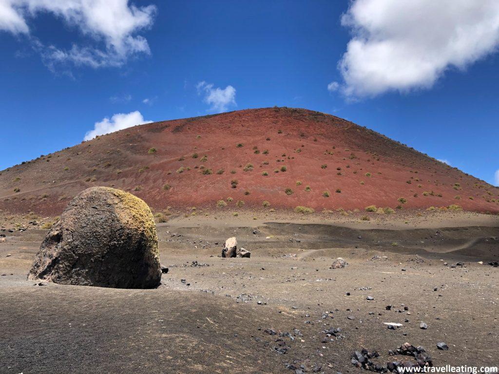 Volcán que presenta un característico color rojizo y una enorme piedra volcánica frente a él.