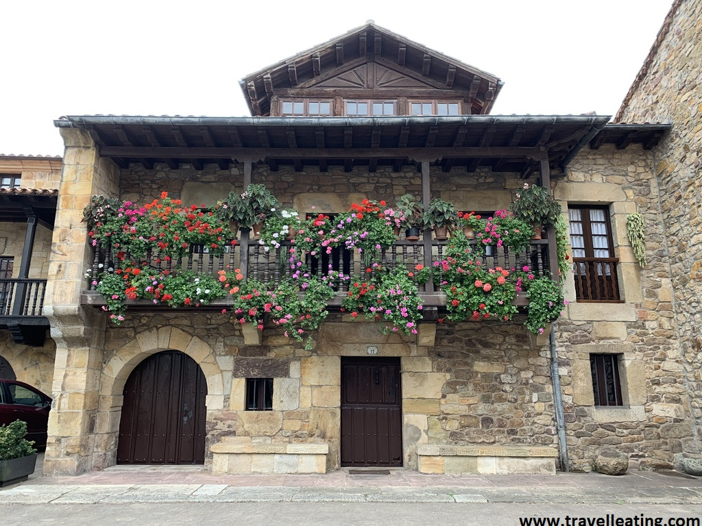 Casa tradicional de piedra con su balcón de madera repleto de flores, en Liérganes, uno de los pueblos imprescindibles de ver en Cantabria.