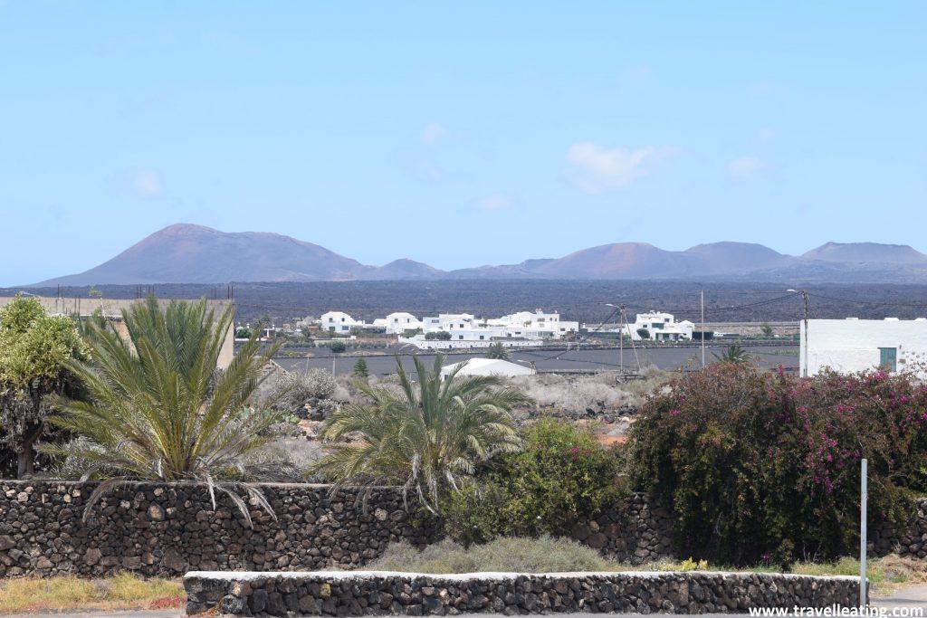 Pueblo blanco rodeado de palmeras, tras el cual se alza un impresionante paisaje volcánico: el Timanfaya. Sin duda uno de los pueblos más bonitos que ver en Lanzarote.