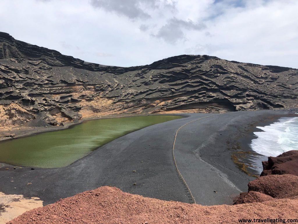 Curiosa laguna verde de origen volcánico que se encuentra a pocos metros de una playa de arena negra y rodeada de tierra volcánica rojiza.