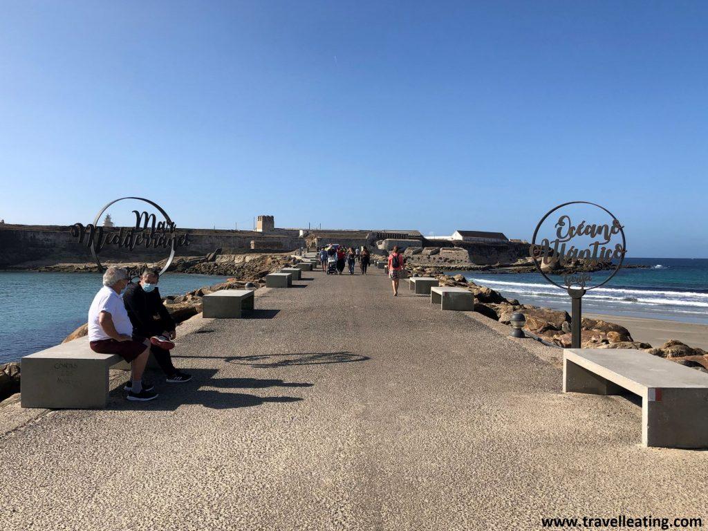 """Pequeña carretera que une Tarifa con una isla. En ella vemos bancos y dos carteles: uno que pone """"Mar Mediterráneo"""" y otro que pone """"Océano Atlántico""""."""