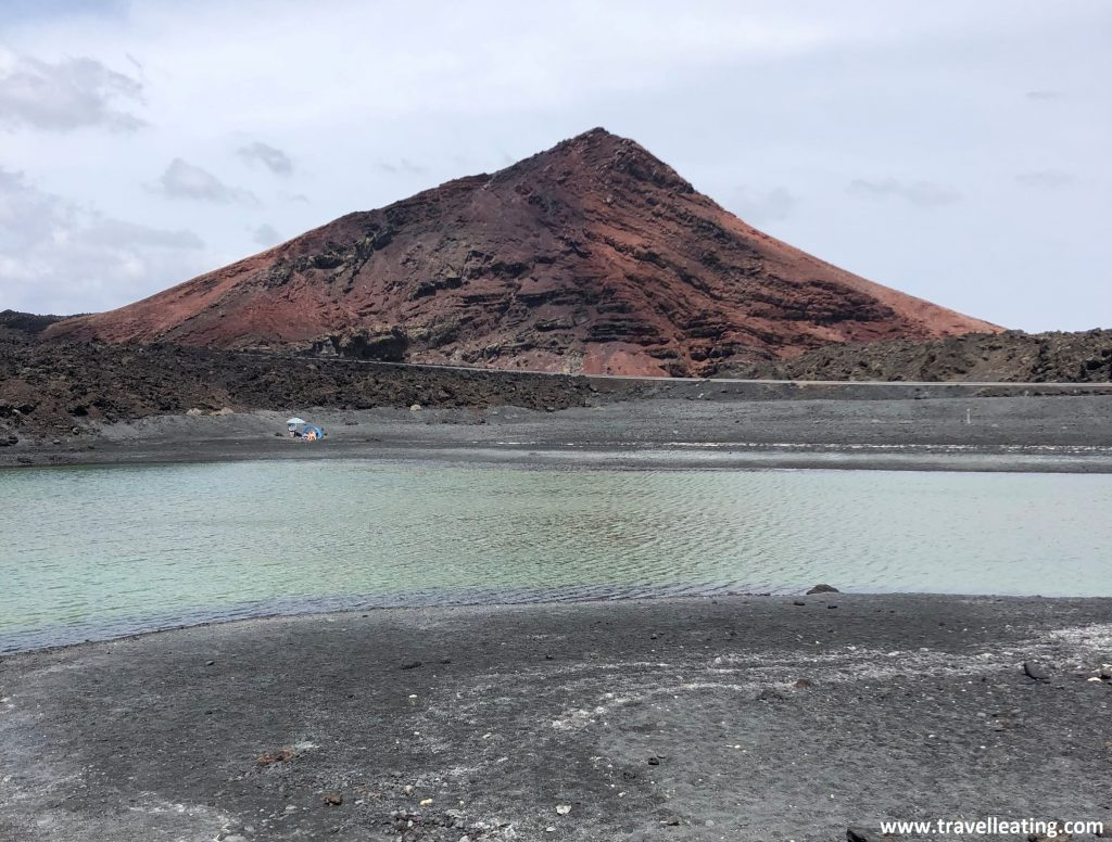 Curioso lago azul situado en la parte trasera de una playa de arena negra y tras el cual se alza un volcán rojo. Uno de los lugares más curiosos que ver en Lanzarote.
