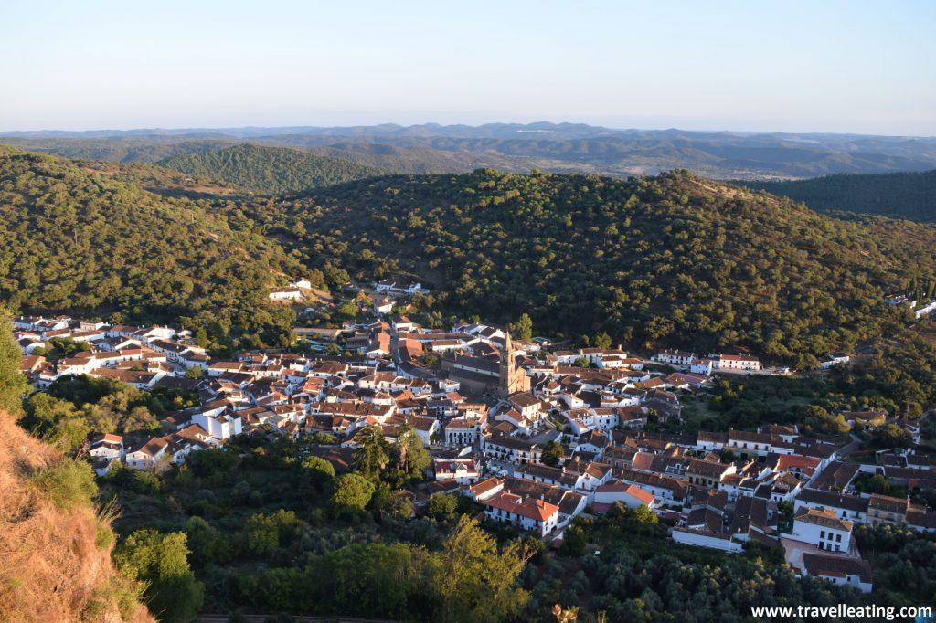 Vistas de un precioso pueblo rodeado por bosques verdes, visto desde lo alto de una colina.