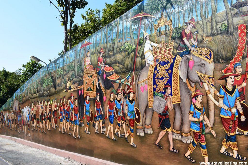 Mural dibujado en una paret en el que se representa una celebración tradicional donde desfilan encima de elefantes.