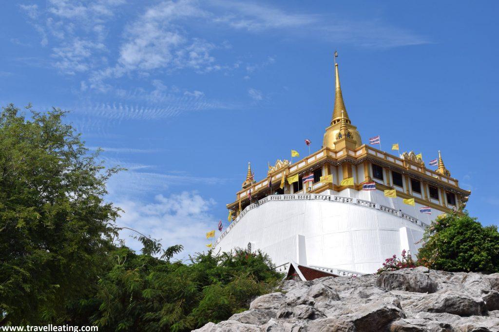 Templo blanco con una pagoda dorada en la parte superior que se encuentra situado encima una colina. Otro de los templos que hay que visitar en Bangkok..