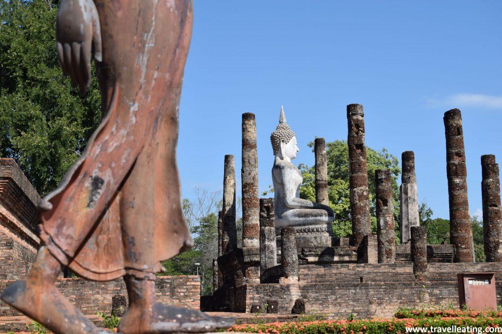 En primer plano a la izquierda tenemos unas piernas de un buda de pie, mientras que el resto de la foto lo ocupa un buda blanco sentado y rodeado de columnas que se encuentra más al fondo.
