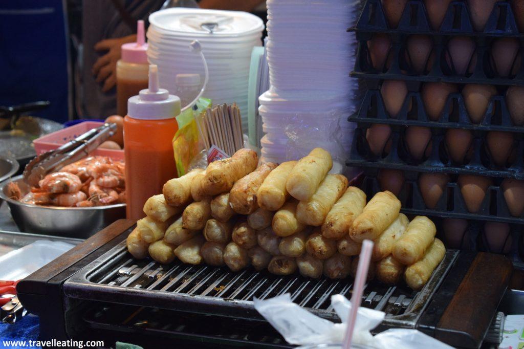 Puesto de comida callejera con rollitos primavera expuestos y apilados en bandejas.