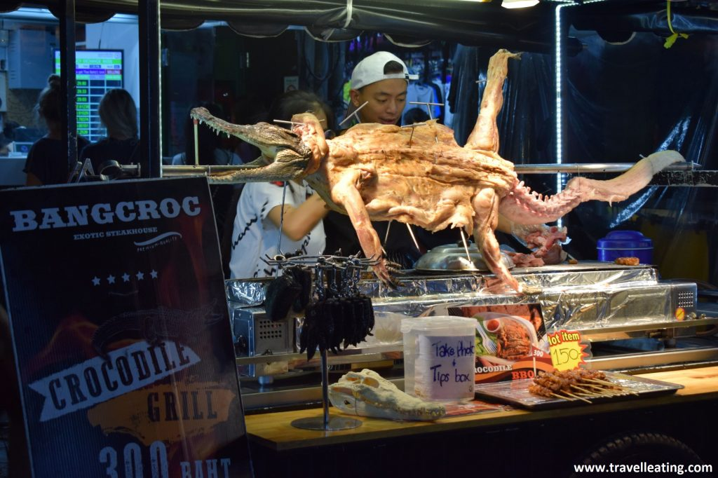 Tienda de carne de cocodrilo en un mercado nocturno de Tailandia. Encima del puesto de comida hay un cocodrilo muerto expueso con las cuatro patas estiradas.