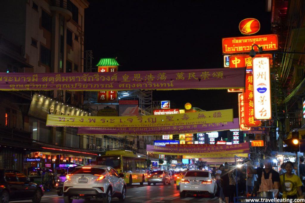 Calle de noche en la que destacan los carteles luminosos que sobresalen de los edificios, así como carteles de tela que van colgados de punta a punta de la calle. Todos escritos en chino y con colores varios.