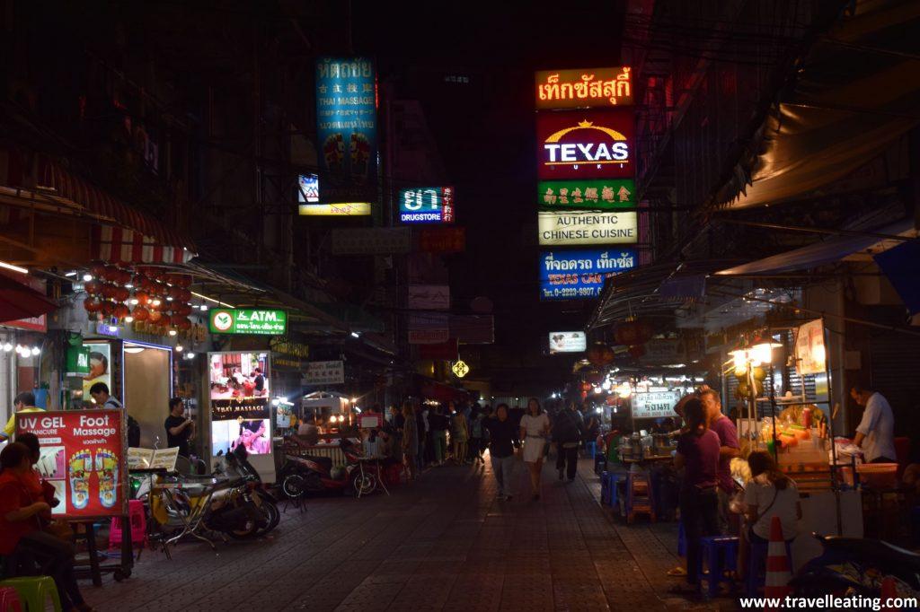 Calle de Chinatown de noche repleta de puestos de comida y carteles luminosos.