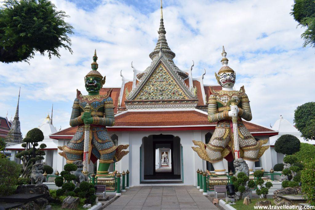 Edificio del complejo del Wat Arun custodiado por dos figuras gigantes de guerreros. Uno blanco y otro verde, ambos sujetando una espada.