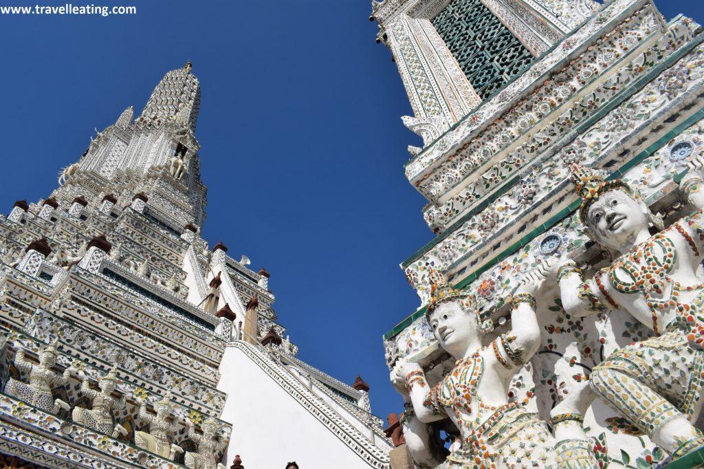 A la derecha vemos un primer plano de las figuras de los guerreros que rodean una fachada del Wat Arun y a la izquierda, más atrás, vemos la torre central piramidal del templo.